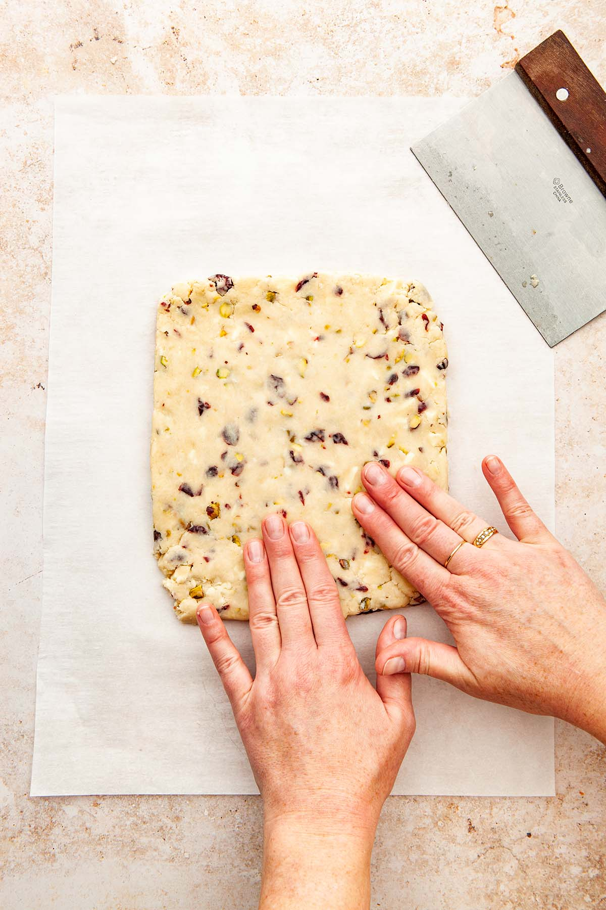 A hand pressing a slab of cookie dough into place before baking.