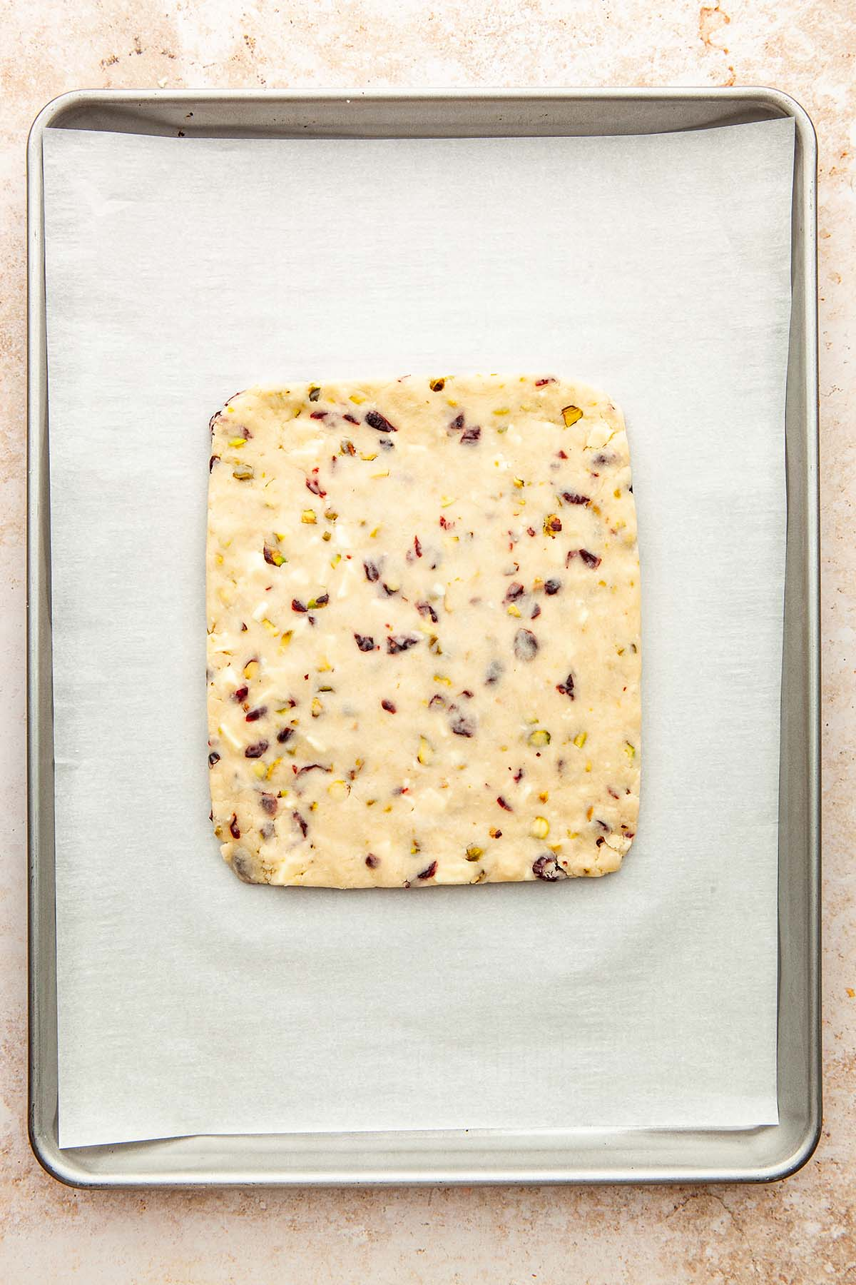 An unbaked rectangle cookie slab on a parchment paper-lined baking sheet.