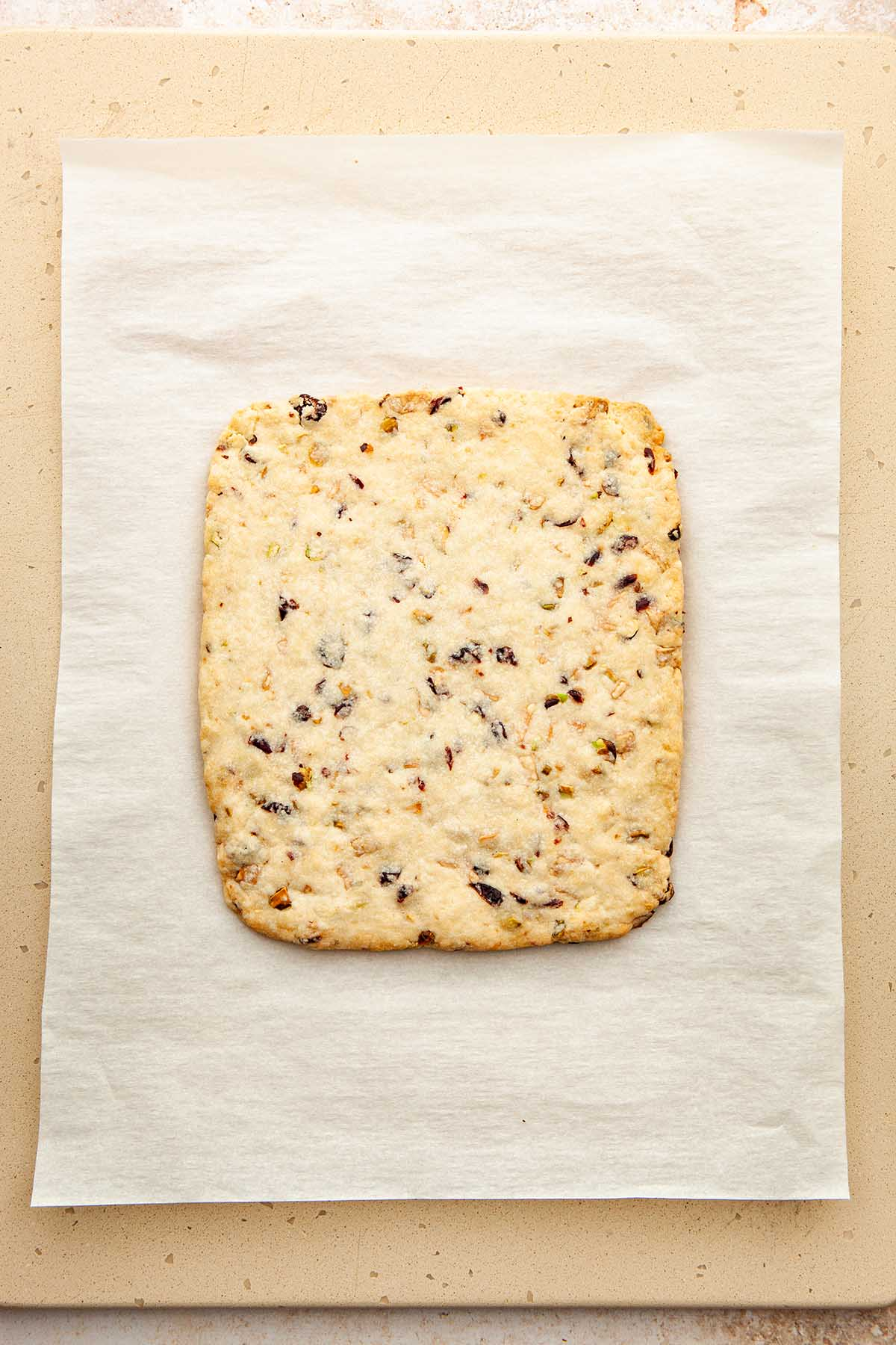 A baked cookie slab on parchment paper.