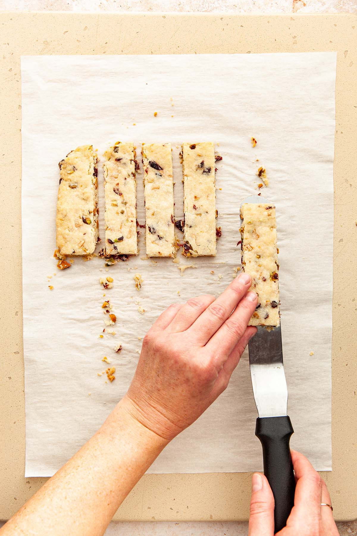 A hand lifting a cranberry pistachio shortbread cookie from parchment paper using an offset spatula.