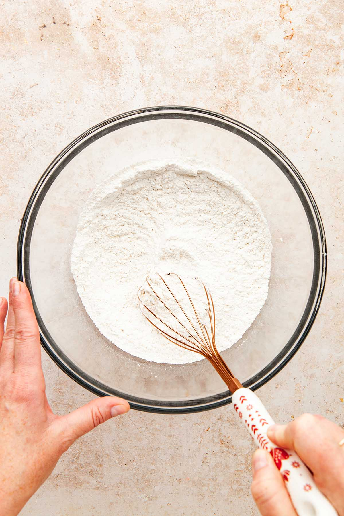 A hand using a whisk to mix flour, powdered sugar, and salt in a large glass bowl.