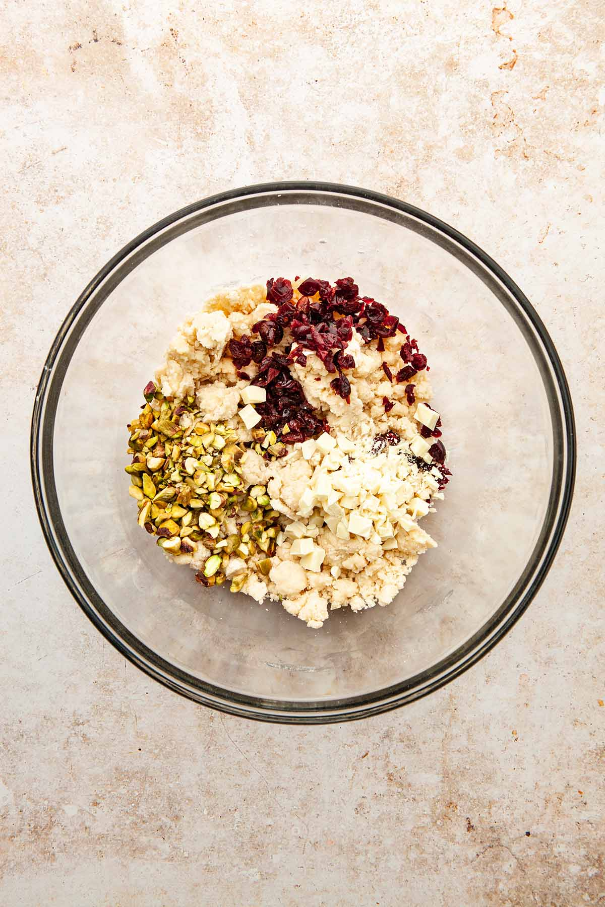 A glass bowl of cookie dough with dried cranberries, chopped white chocolate, and chopped pistachios on top about to be mixed in.