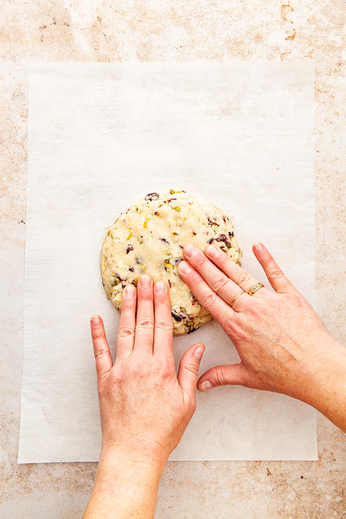 Hands pressing cookie dough into a disc on parchment paper.