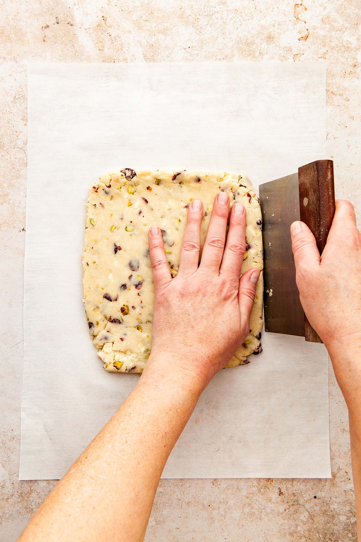 Hands shaping cookie dough into a perfect rectangle using a bench scraper.
