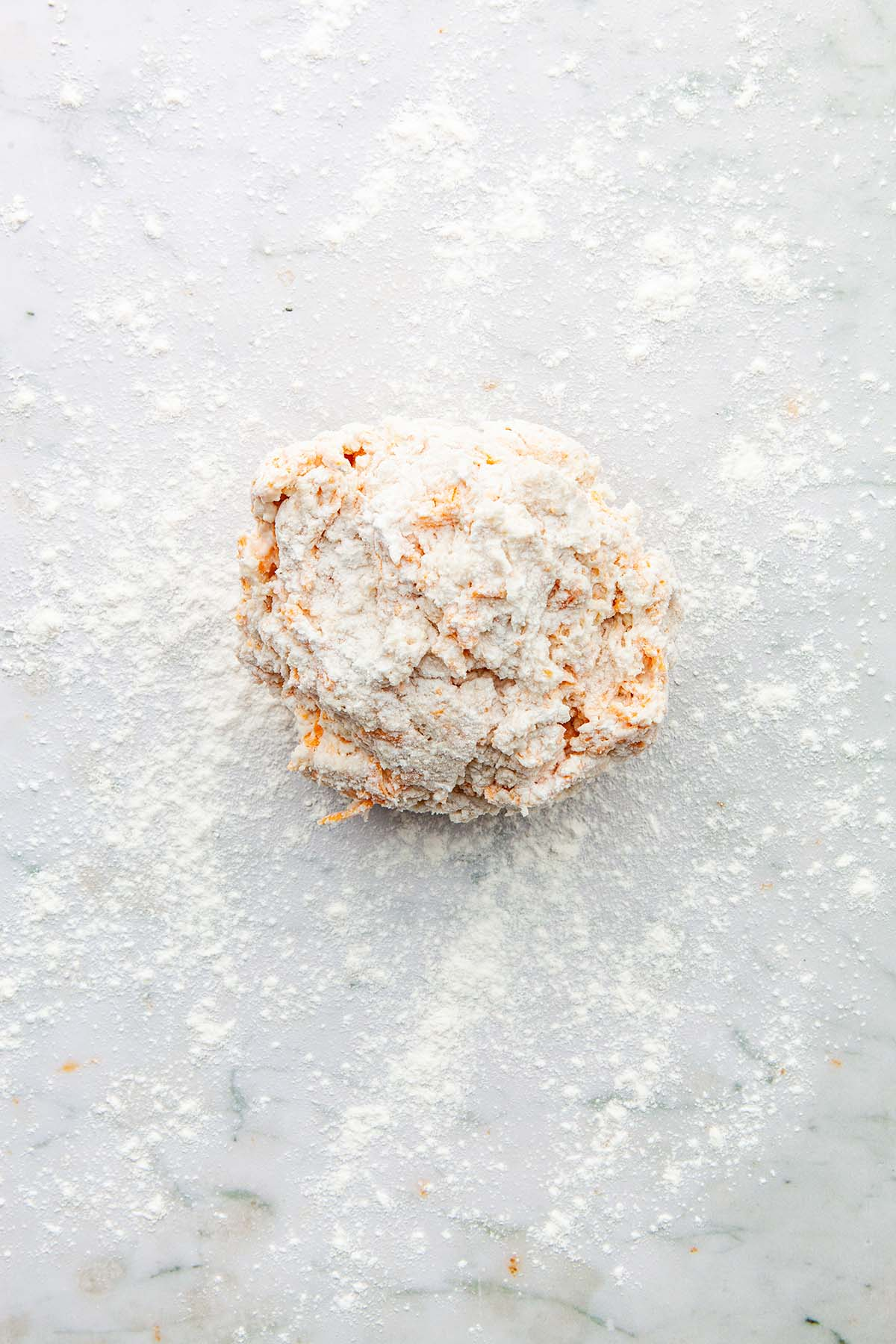 A ball of dough on a floured marble surface.