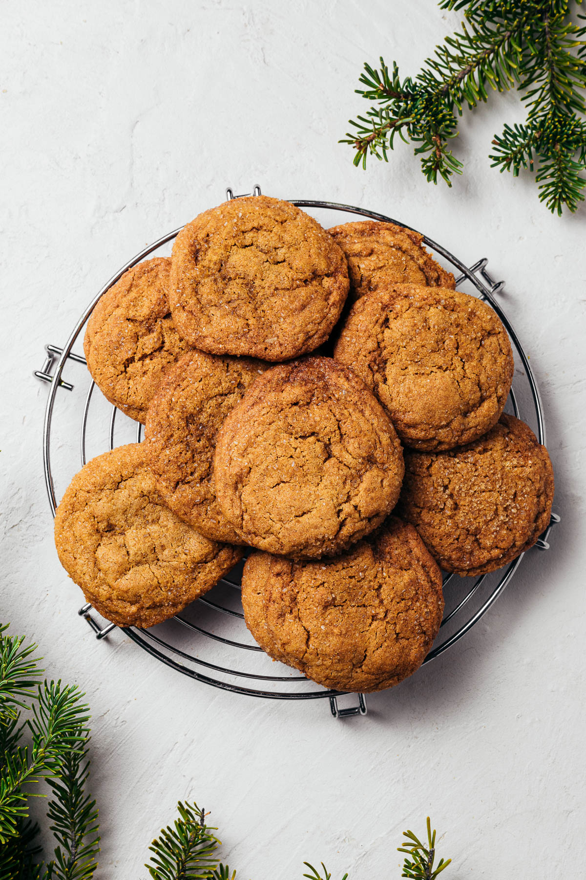CoSugar & spice cookies on a round cooling rack with evergreen branches peeking in the corners.