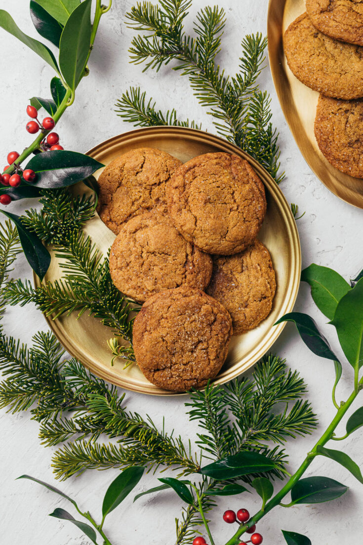 Sugar & spice cookies on a gold plate surrounded by evergreen branches and holly.