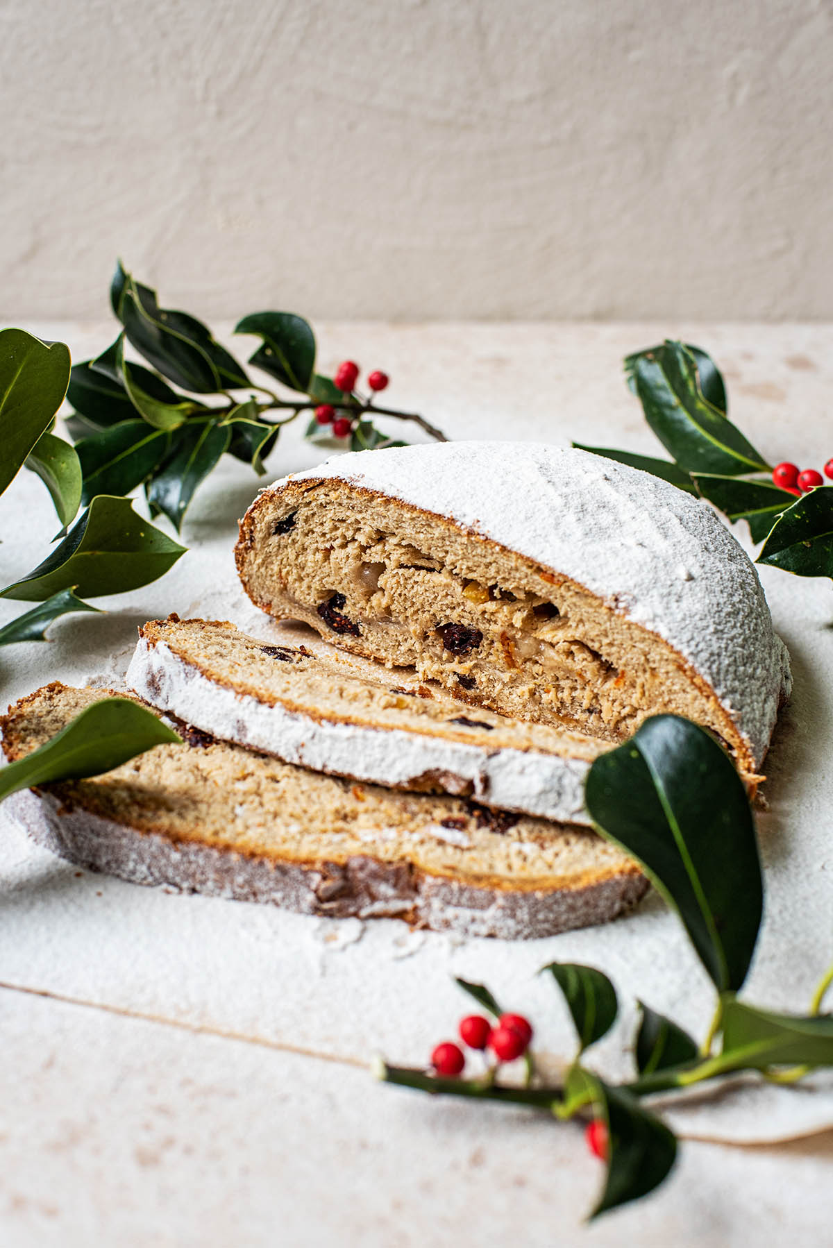 Stollen with two slices cut and holly surround.