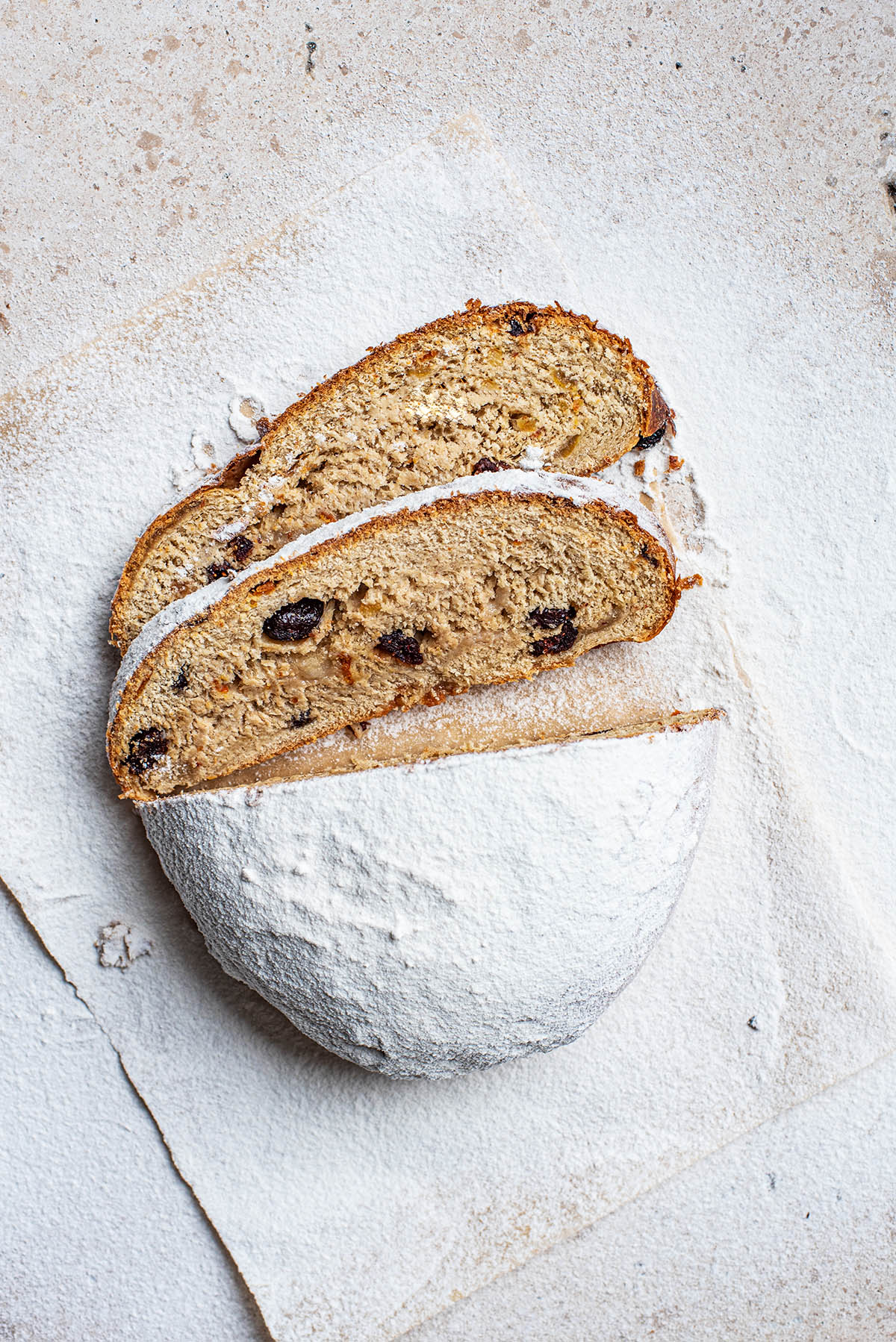 Icing sugar coated stollen with two slices cut.