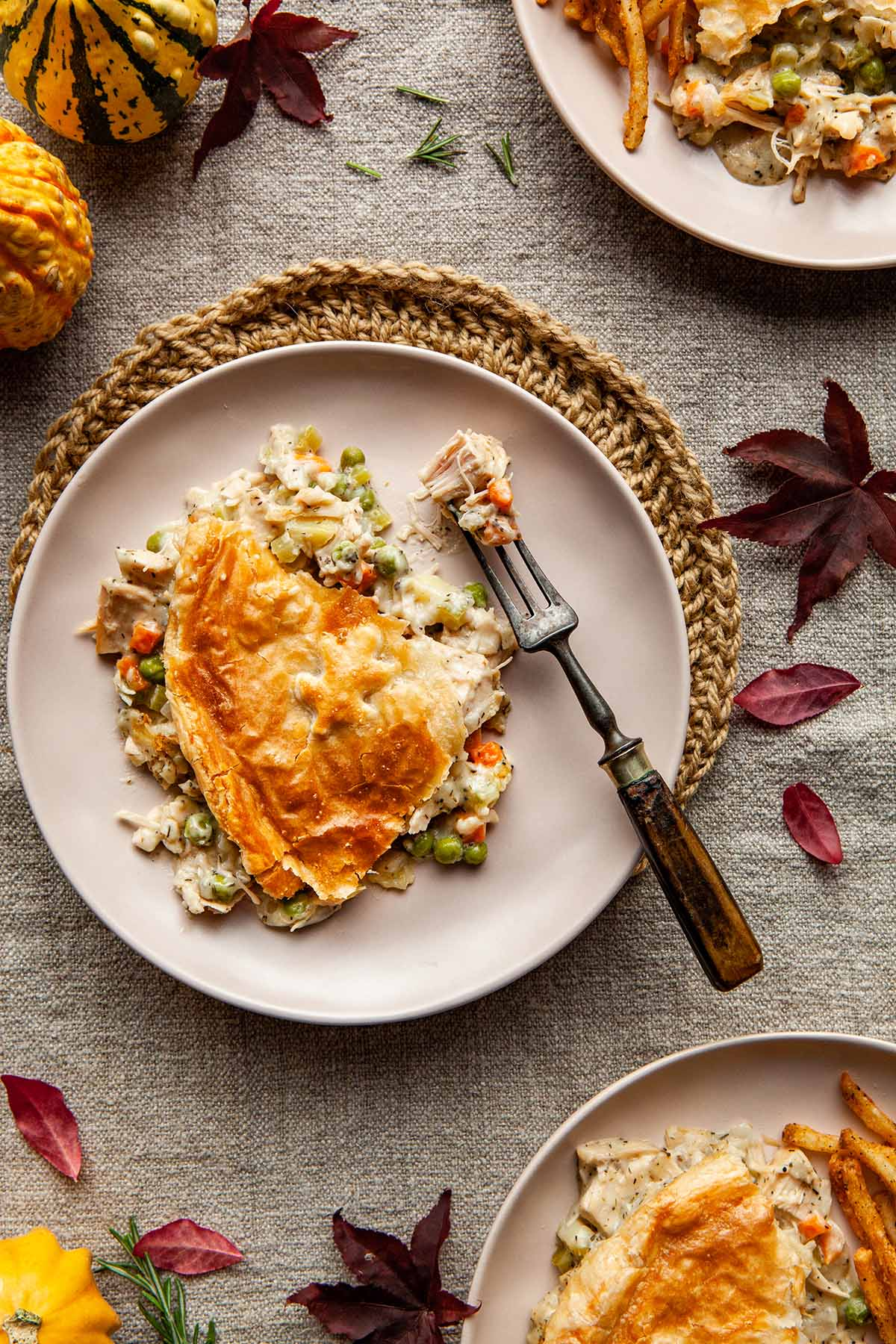 A serving of puff pastry turkey pot pie on a plate with fork and some fall decorations around the table.