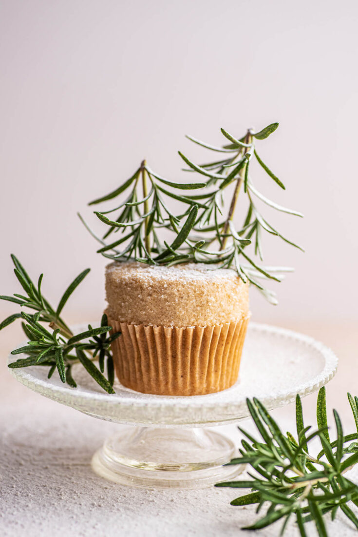 A vanilla cupcake topped with buttercream and rosemary trees on a small platter.