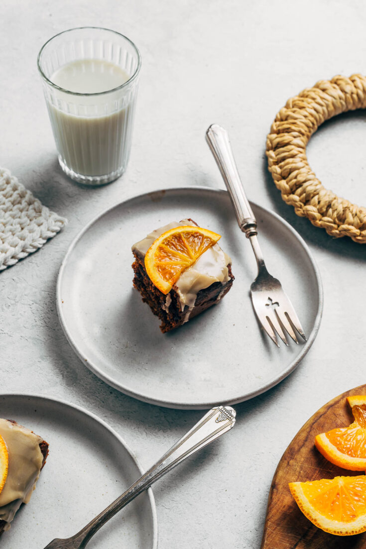 Small square of cake topped with an orange slice on a plate.