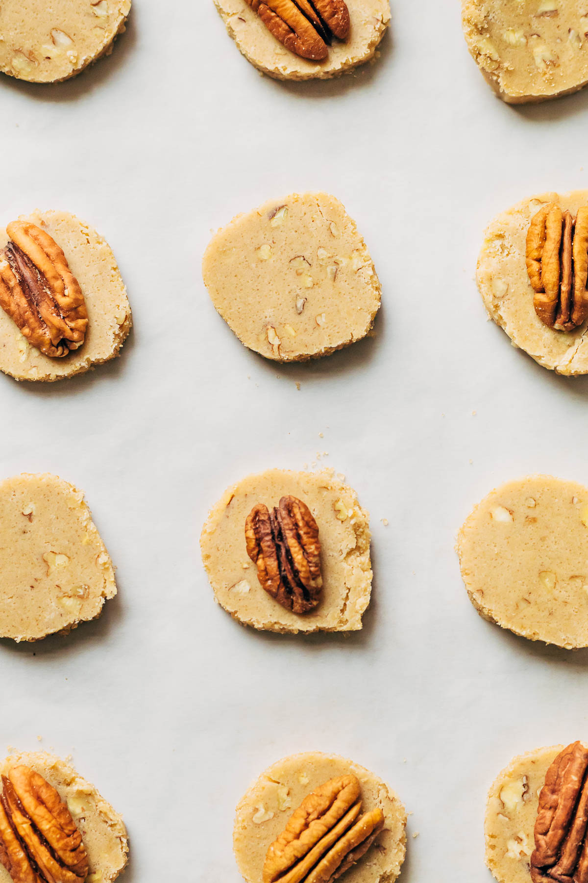 Unbaked sliced icebox cookies on parchment paper.