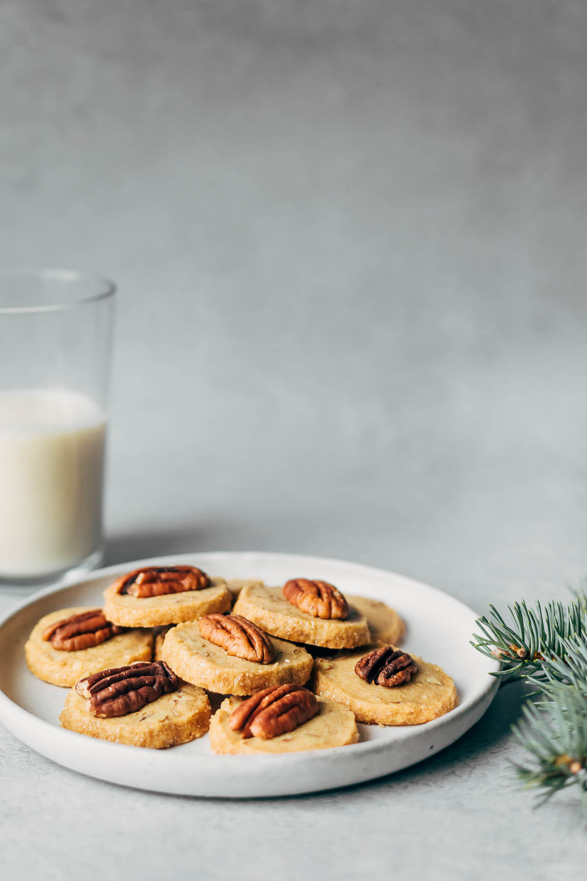A plate of pecan shortbread cookies with a glass of milk in the background.