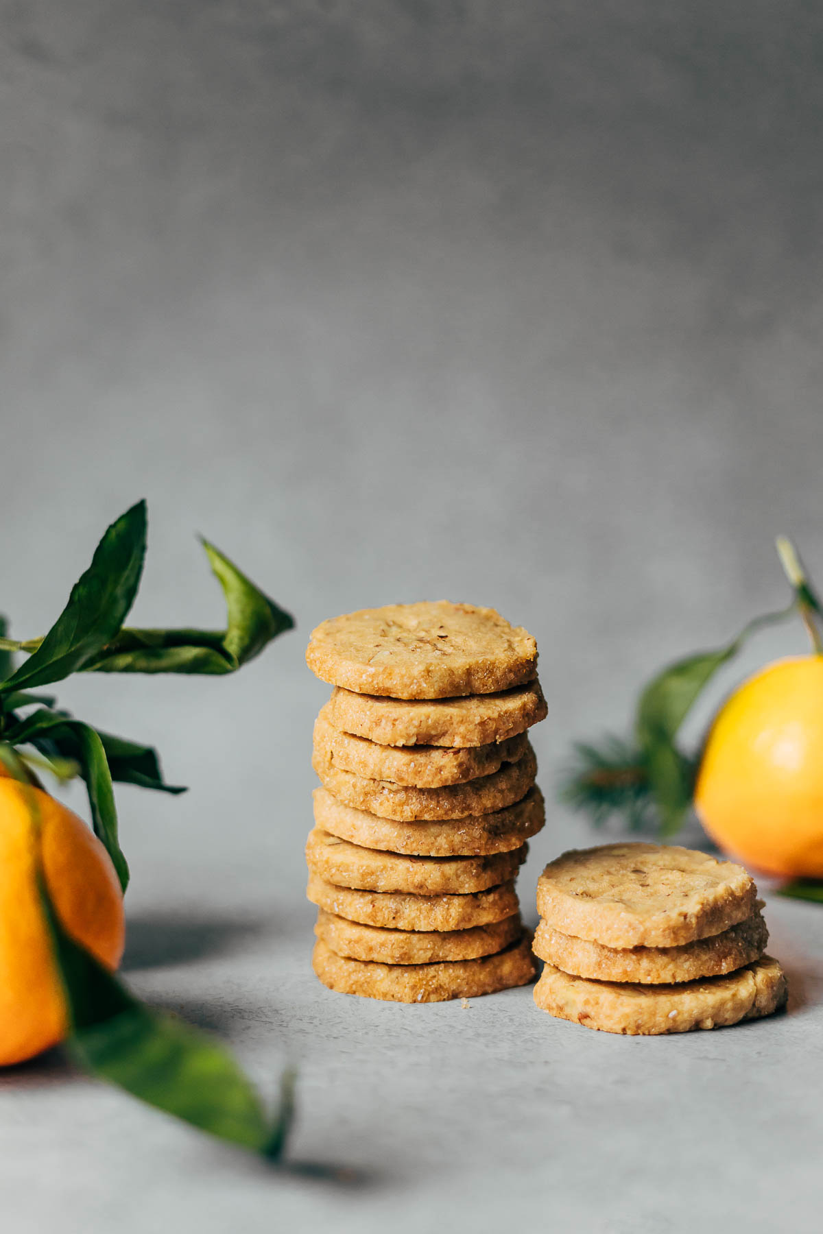 Two stacks of pecan shortbread cookies with clementines in the foreground and background.