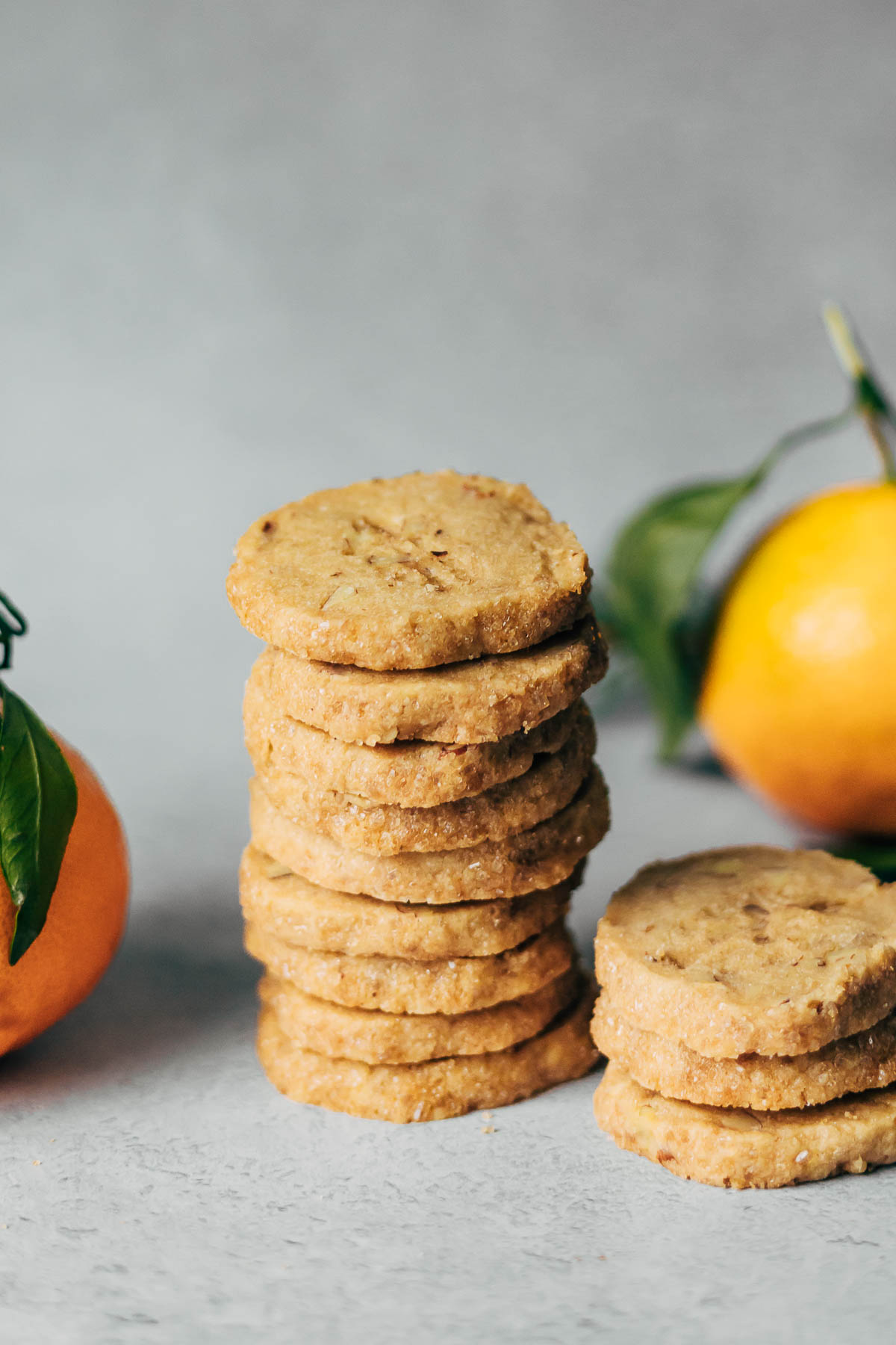 A stack of pecan shortbread cookies with whole clementines nearby.