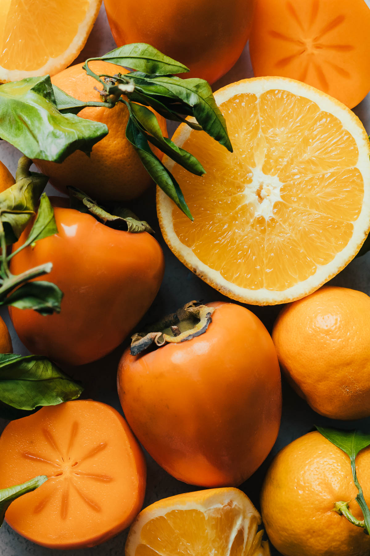 Sliced oranges with leaves and persimmons.