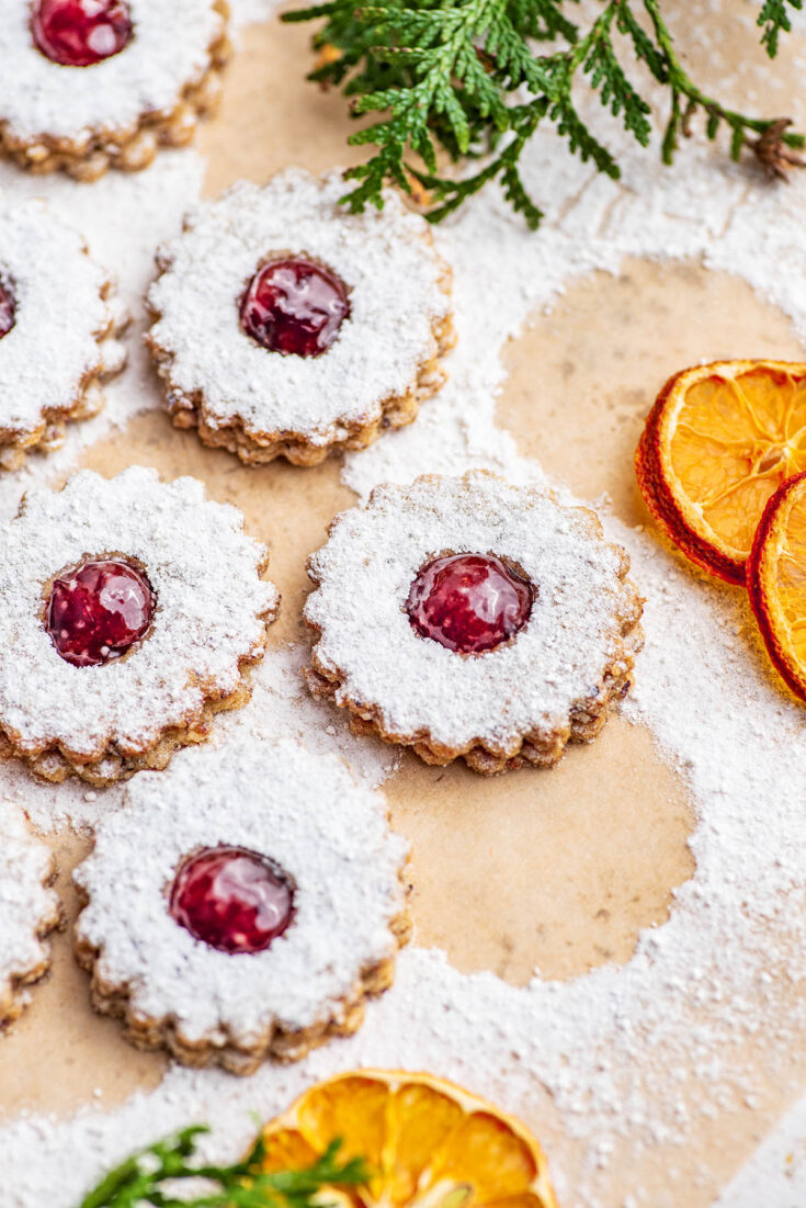 Close up of linzer cookies with dried oranges and greenery.