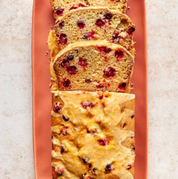 A half-sliced cranberry orange loaf on a coral-pink rectangle platter with rounded corners.