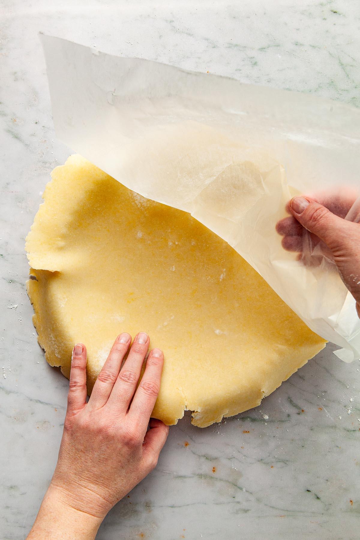 Placing rolled dough into a tart tin.
