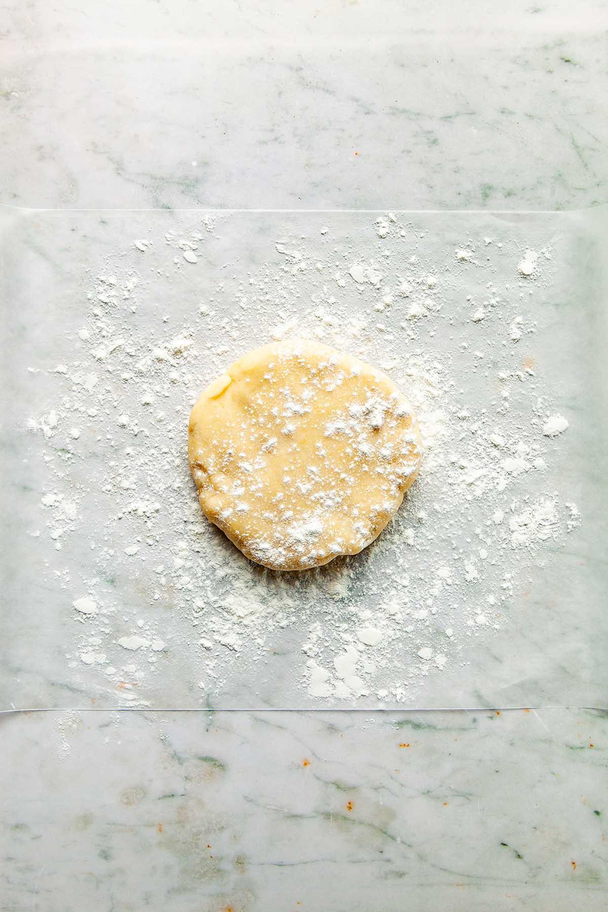 A disc of dough on a floured surface.