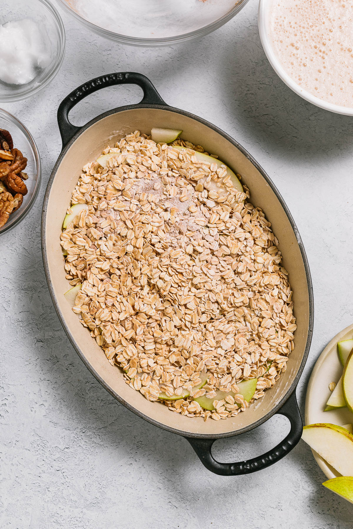 An oval baking dish of uncooked oats and sliced pear.