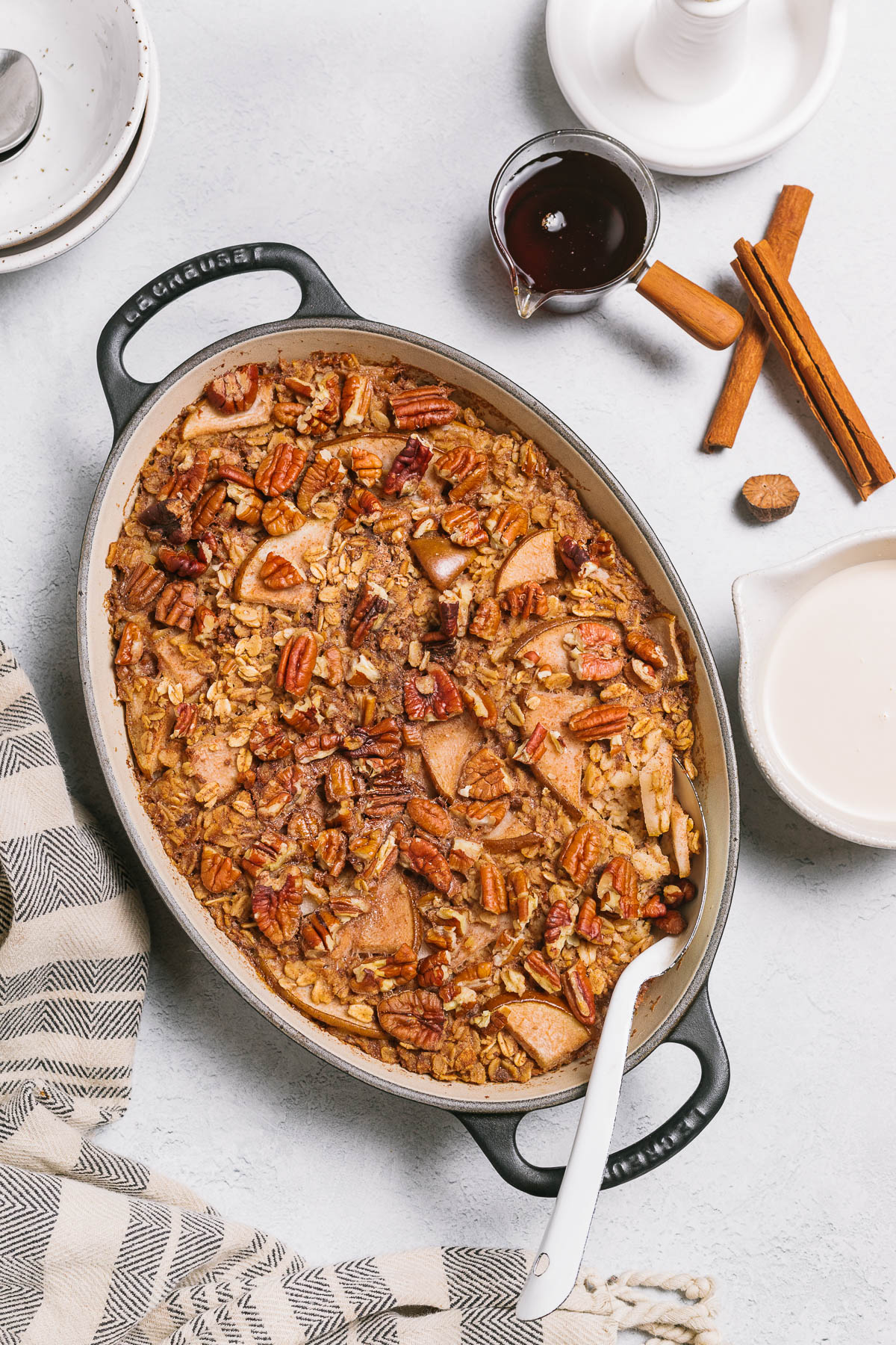 An oval baking dish of vegan baked oatmeal with pears and pecans.