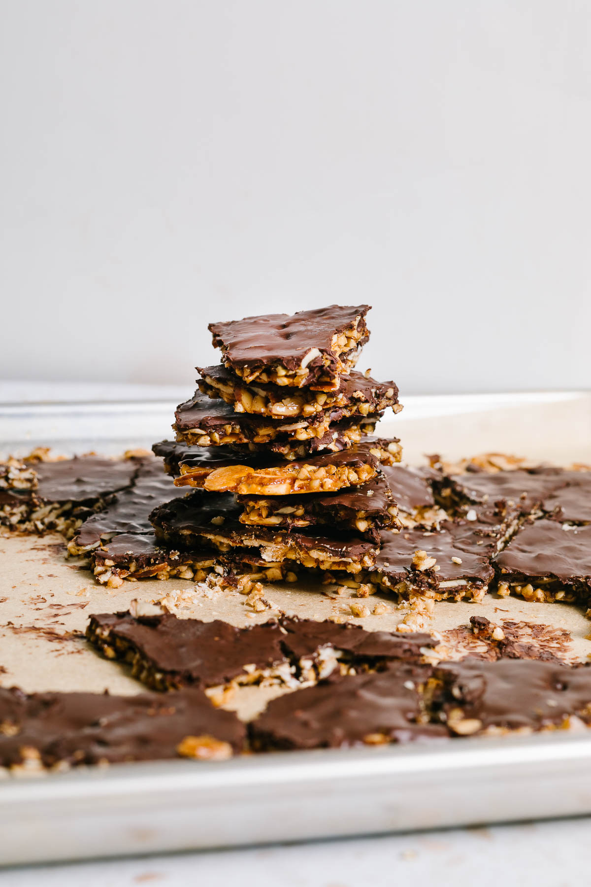 A stack of vegan almond brittle stacked on a baking sheet.