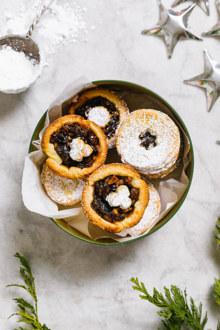 Mincemeat tarts in a tin with Christmas decorations around.