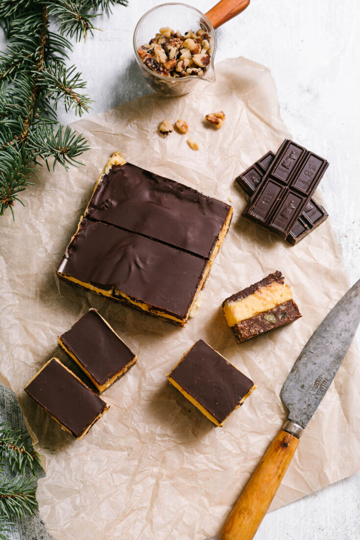 Bars on parchment paper with greenery and nuts.