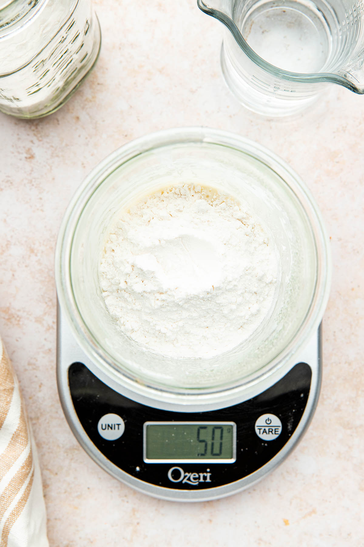 A jar of flour and water on top of a digital scale reading 50 grams.