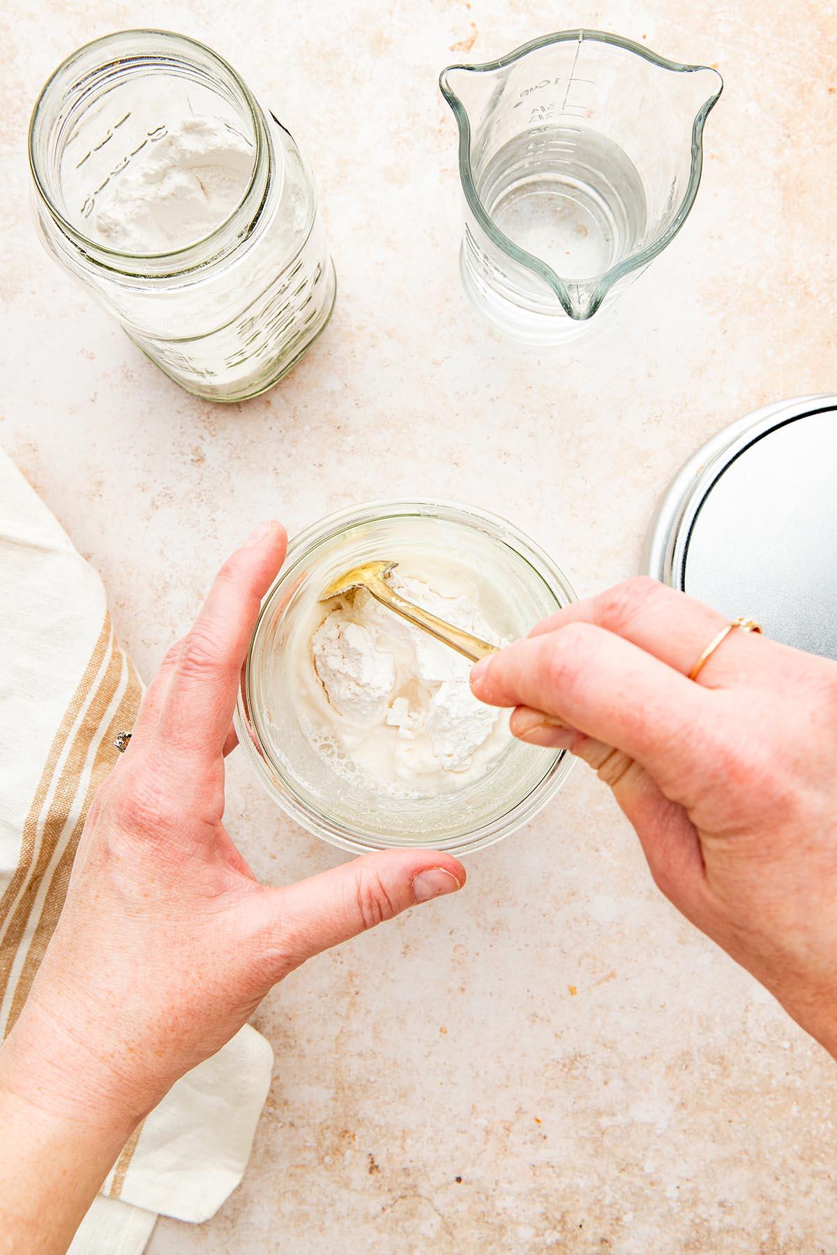A hand using a. long spoon to stir a jar of sourdough starter.