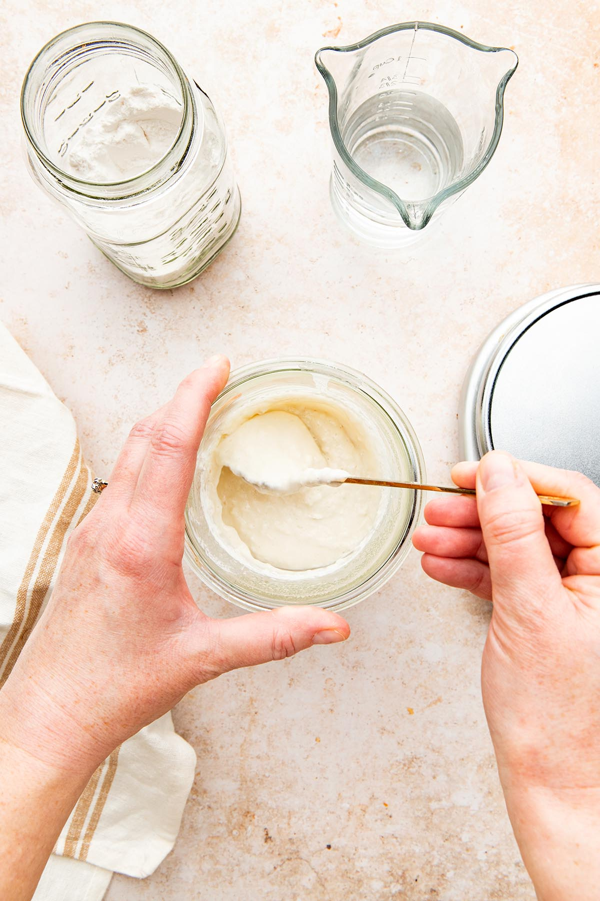A hand using a spoon to mix a jar of sourdough starter.