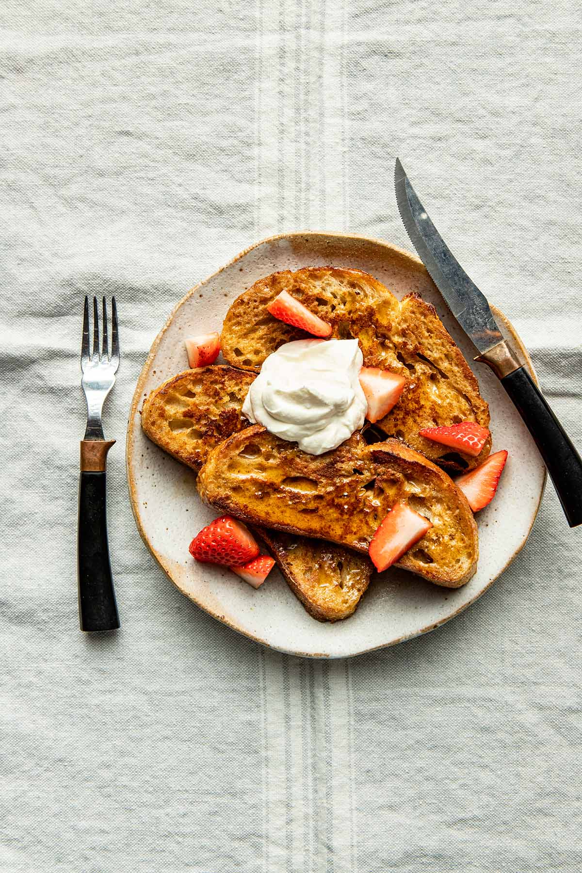 Souroudhg French toast on a plate with strawberries, maple syrup, whipped cream, and a knife and fork.