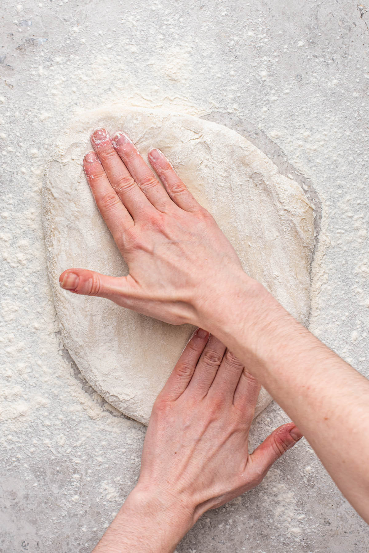 Patting out the dough into a rectangle.