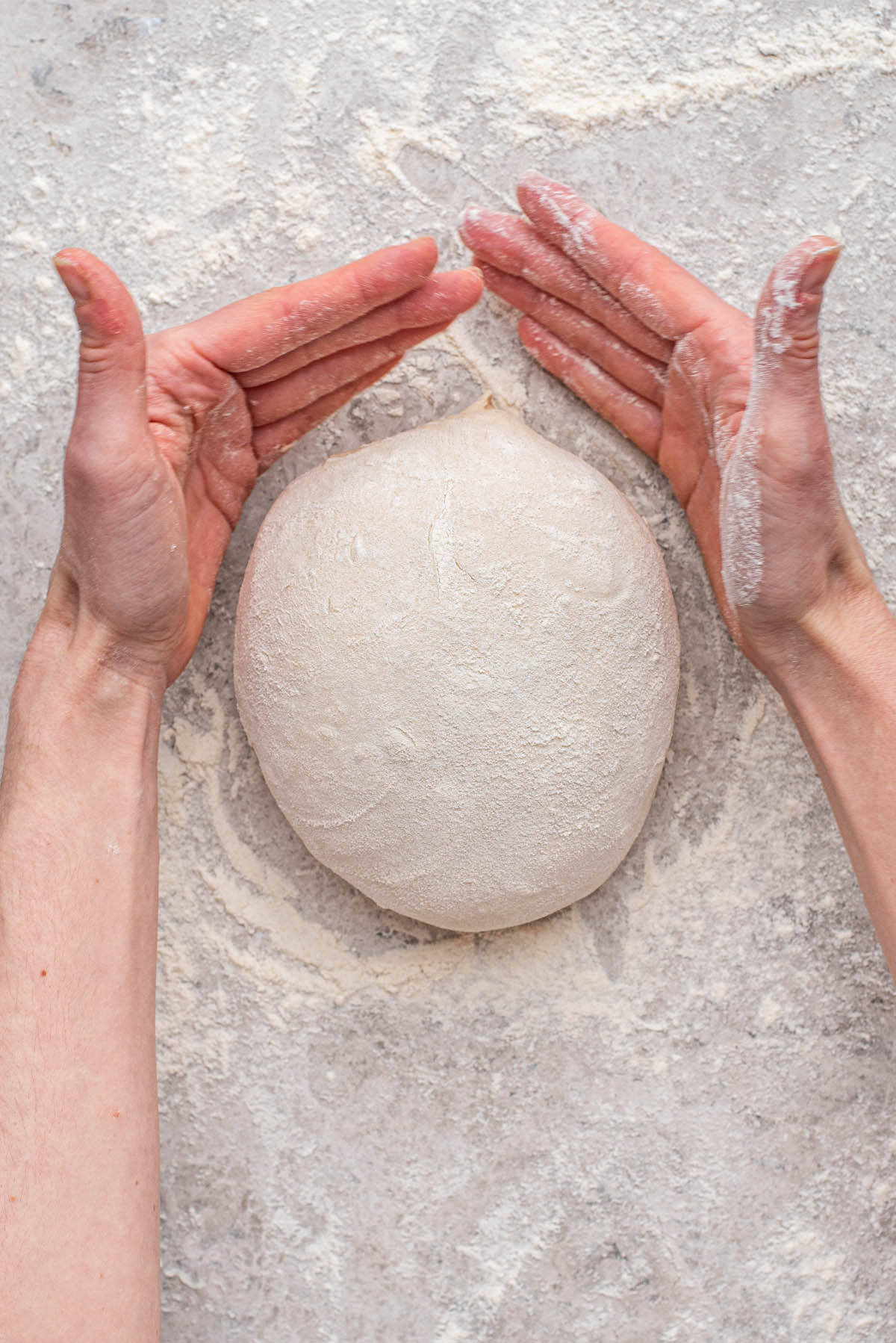 Rotating the ball of dough with two hands.