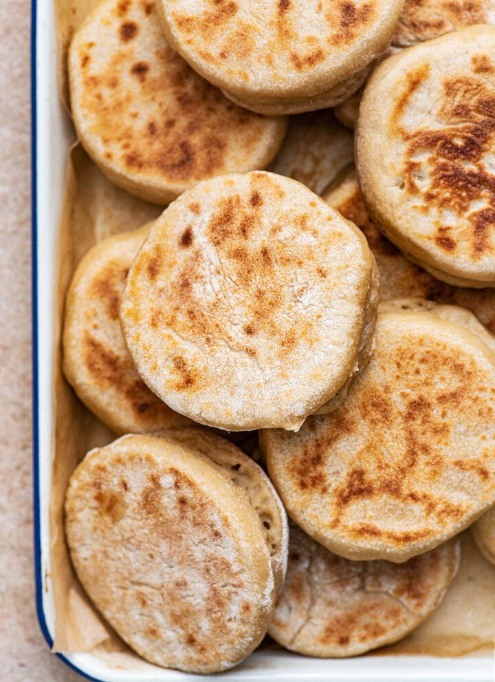 A pile of English muffins in a shallow tray.