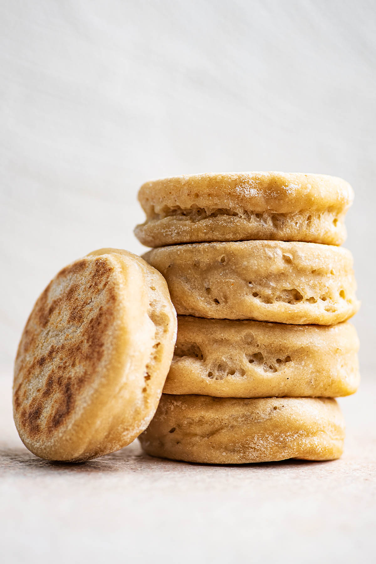 A stack of four English muffins with one leaning against it.