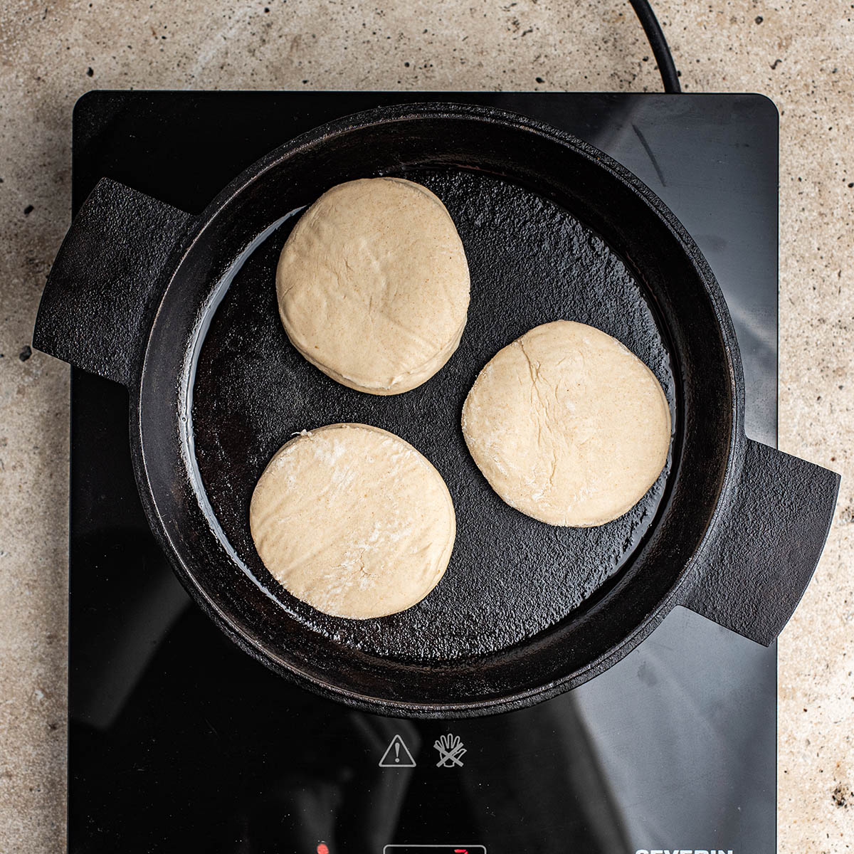 Frying the English muffins in a cast iron pan.