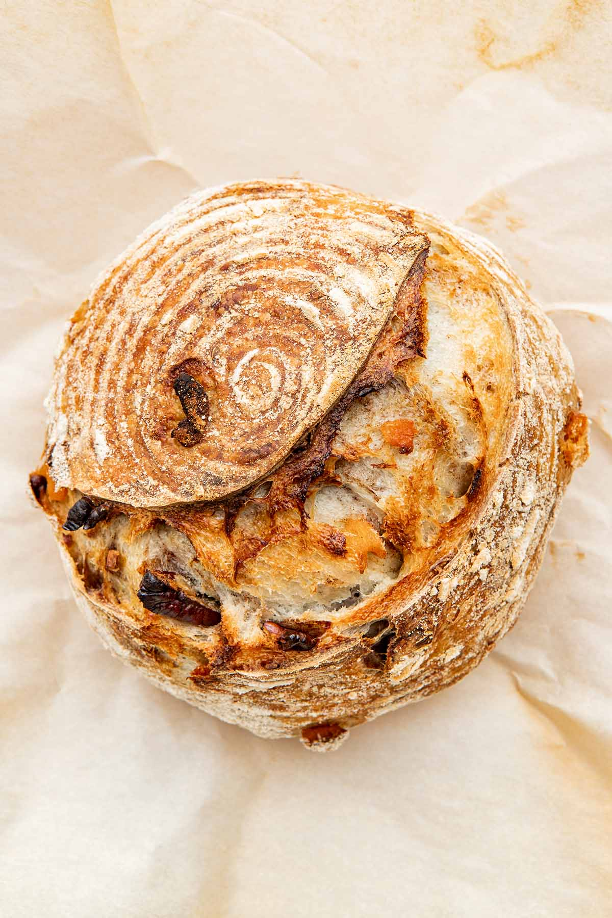 Close up of a loaf of sourdough bread on parchment paper.