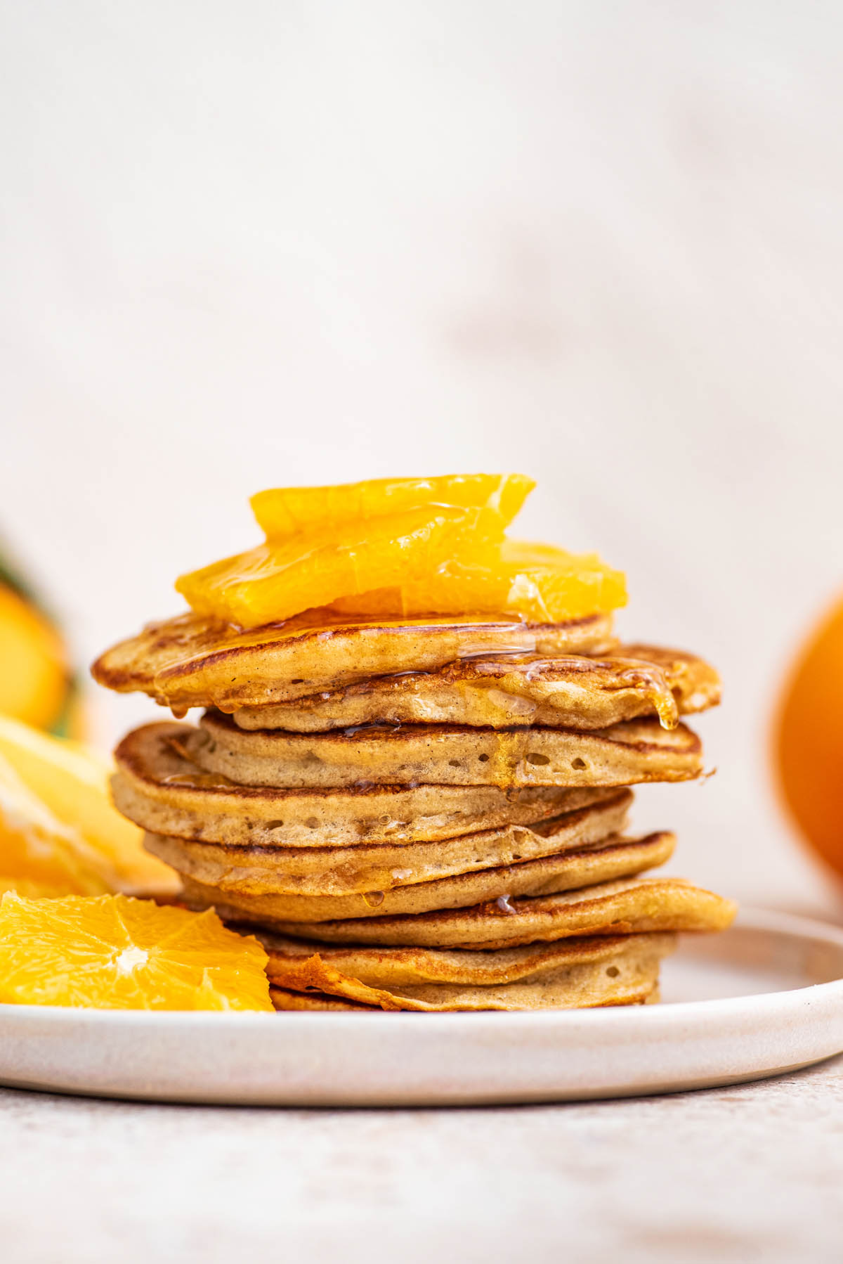 A stack of sourdough starter pancakes and oranges slices.
