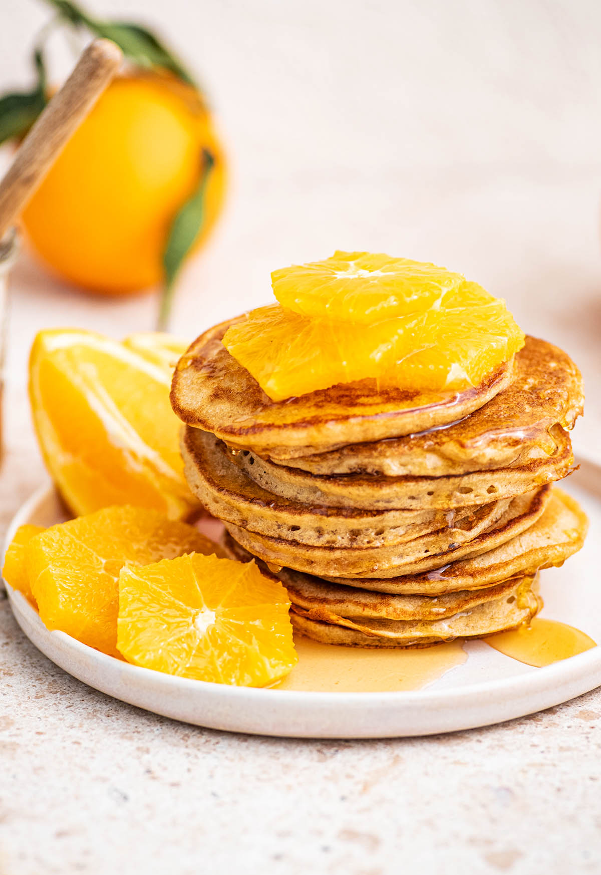 45º angle shot of a stack of sourdough starter pancakes on a plate with oranges.