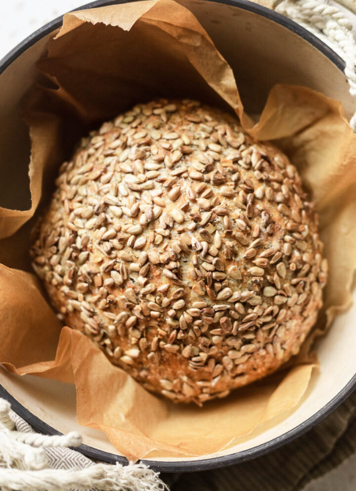 A loaf of sourdough bread in a pot with sunflower seeds.