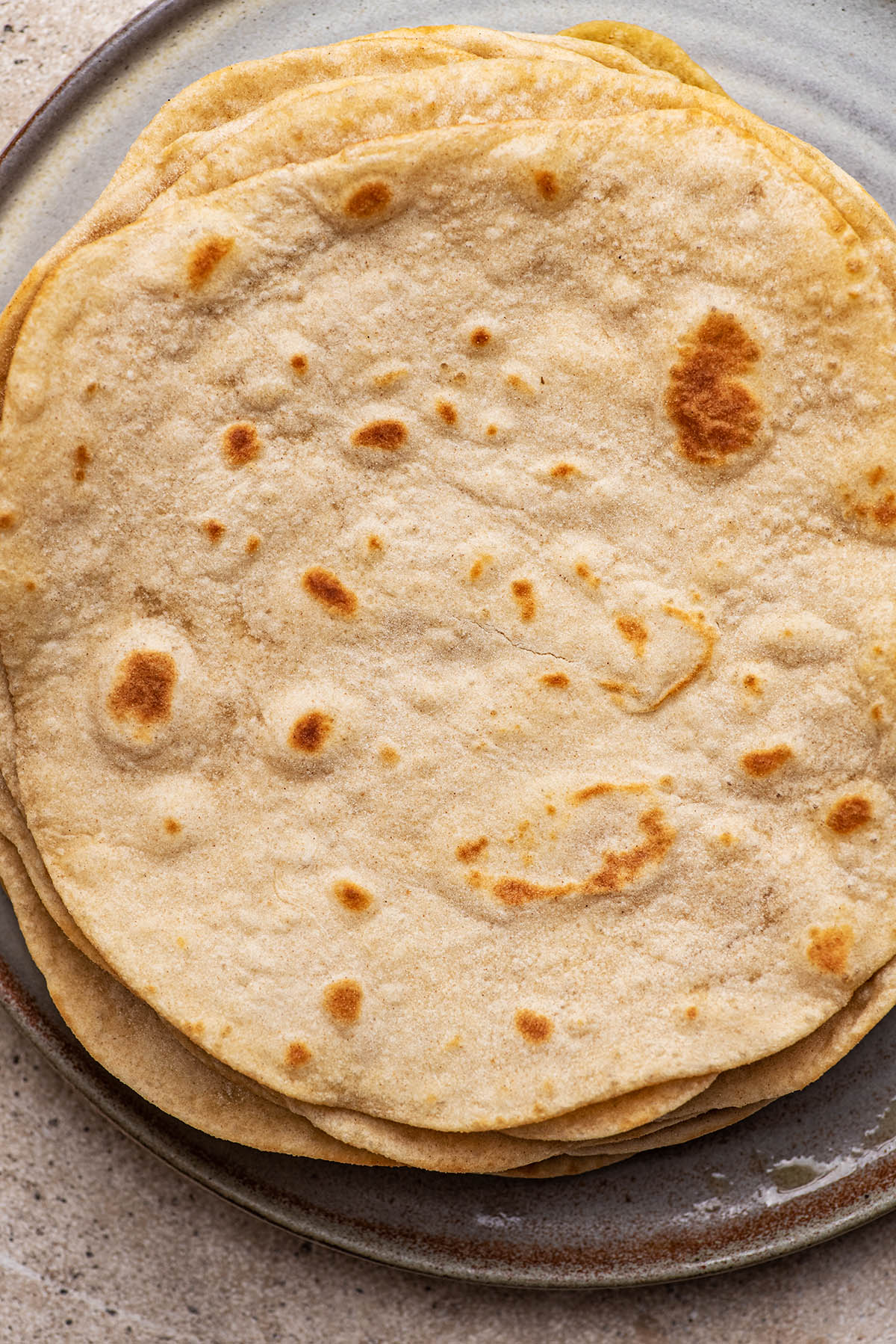 Sourdough tortillas stacked on a plate.