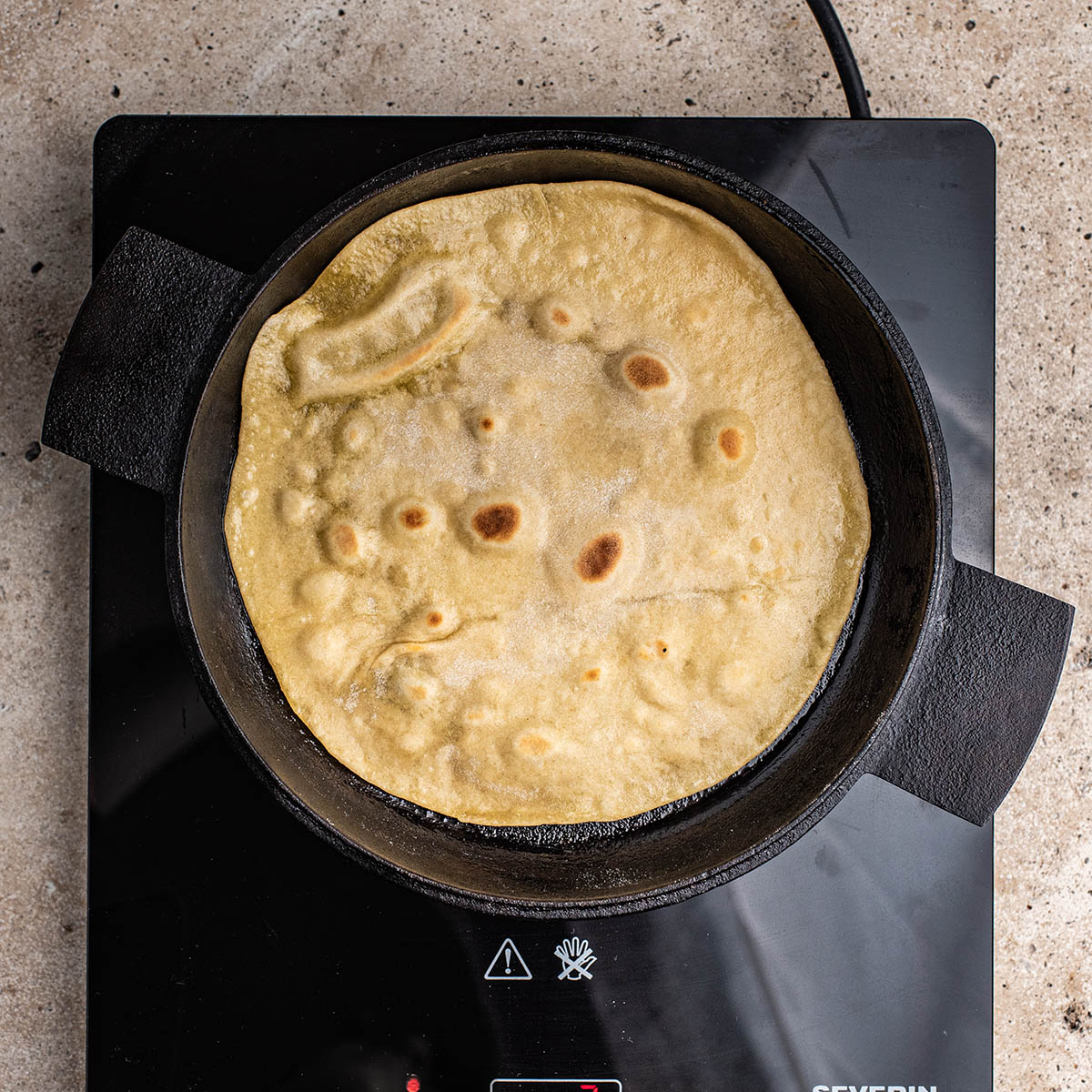 Tortilla in a frying pan after flipping.