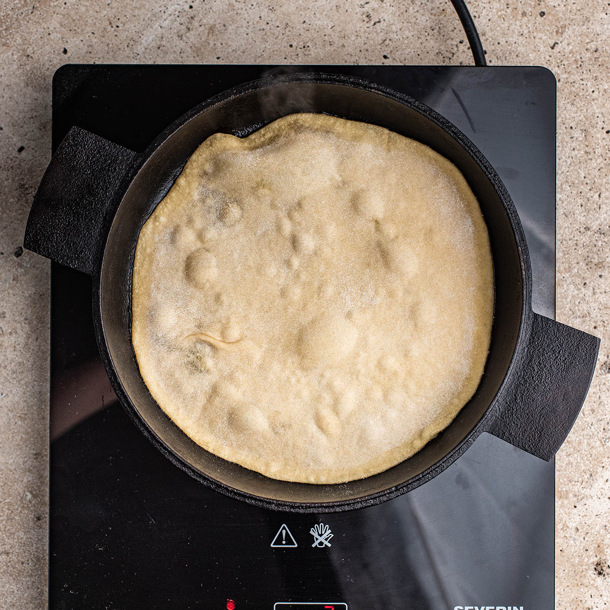 Tortilla in a frying pan before flipping.
