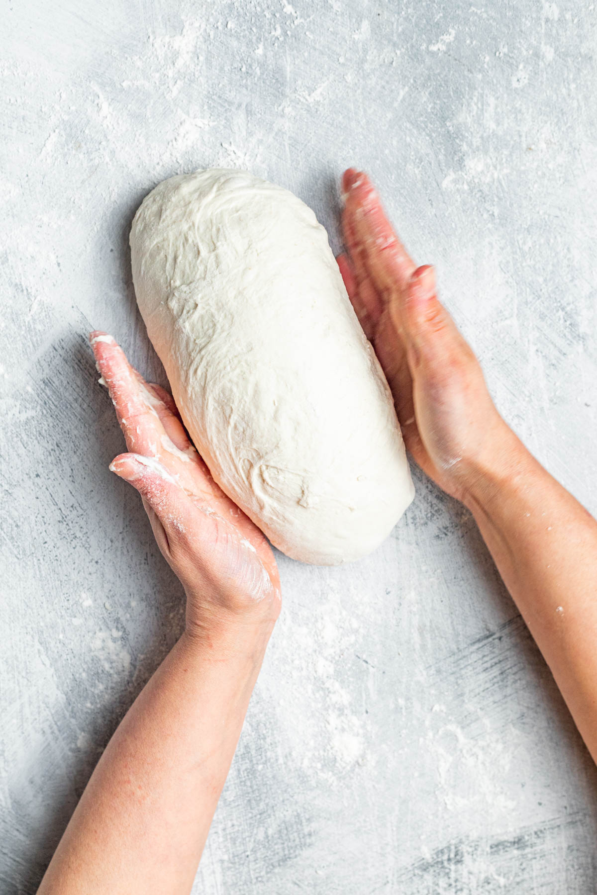 Woman's hands shaping dough into a log.