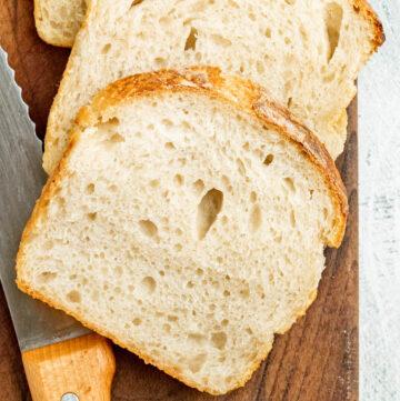 Sandwich bread on a cutting board with a knife.