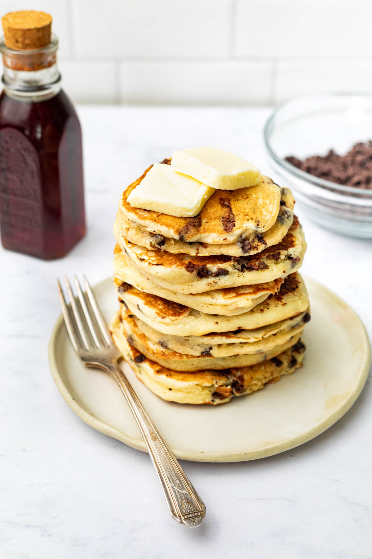 A stack of several chocolate chip pancakes with butter.