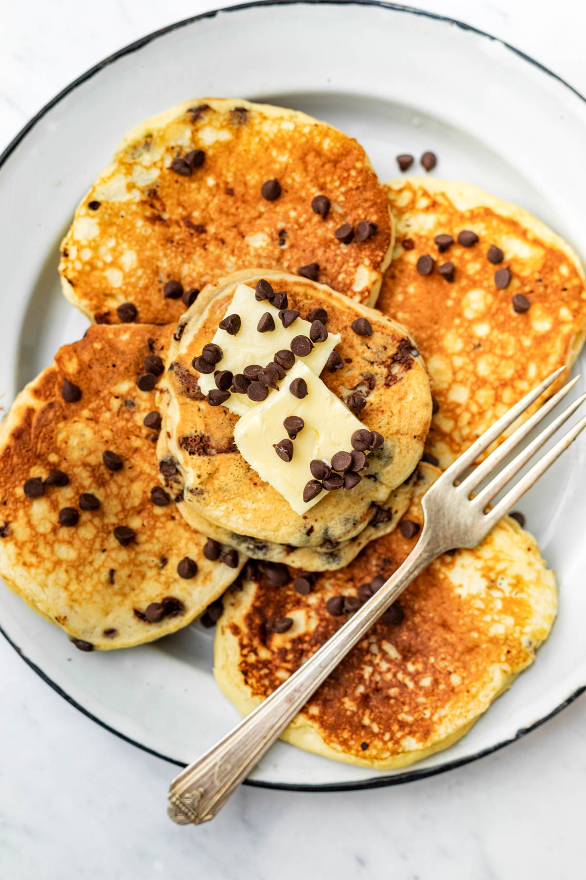 Pancakes on a plate topped with butter and mini chocolate chips.